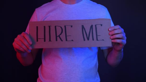 Man holding cardboard with hire me and need job inscriptions