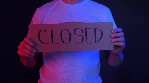 Front view of unemployed man holding cardboard with closed text