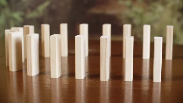 Wooden domino blocks falling down on flat wooden table