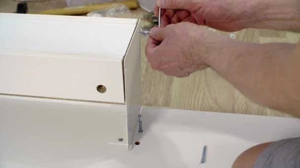 Šroubování rukou šestihranný šroub v bílém prkně