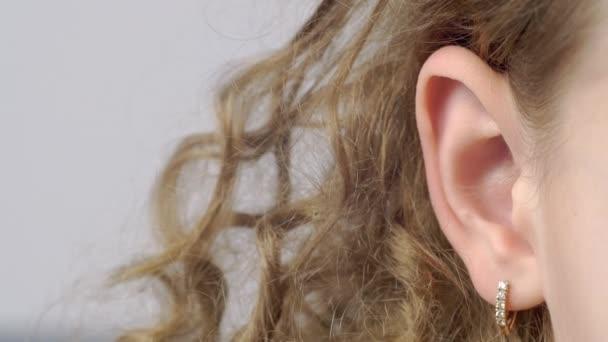 Nahaufnahme weibliches Ohr mit Ohrringen Vorderansicht. Rechtes Ohr einer lockigen jungen Frau auf grauem Hintergrund. Menschliche Hörorgane. Menschliches Körperteil. Kopfanatomie.