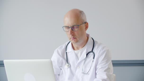 Serious doctor working with laptop computer and thinking about diagnosis