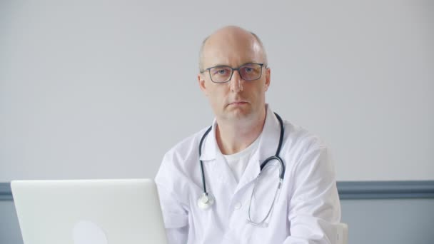 Portrait bald male doctor nodding head sitting on table front laptop in medical office. Practitioner doctor listening patient online front notebook in clinic.