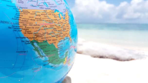 Earth globe on sandy beach. Summer trip to Maldives