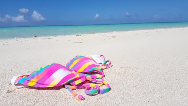 Striped bikini on the beach. Summertime relax in Bali.