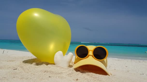 Yellow balloon with cap, coral and sunglasses on tropical beach, Maldives.