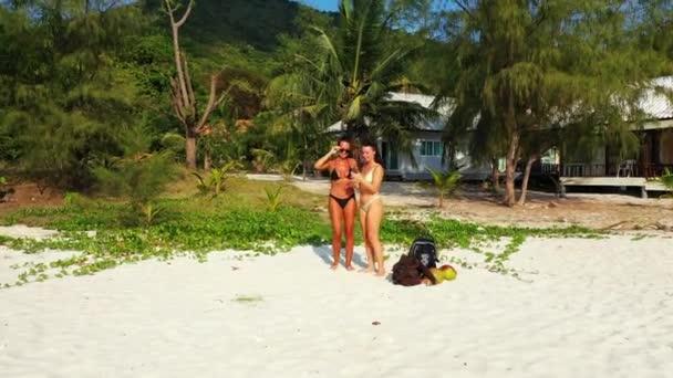 Két fiatal barátnő áll a homokos tengerparton, fotóznak és néznek mobilon az egyik lányról. Gyönyörű nők pihennek trópusi üdülőhelyen