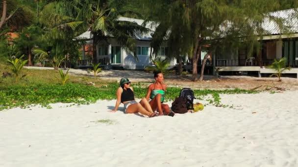 Két fiatal barátnő ül a homokos tengerparton, zacskókkal a mellettük és beszélgetnek. Gyönyörű nők pihennek trópusi üdülőhelyen