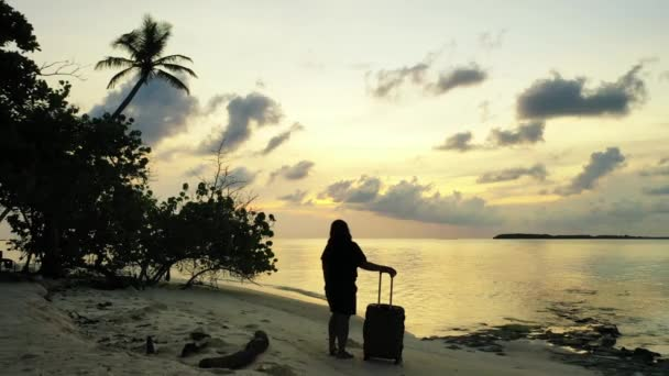 Silhouette of  woman with luggage on the beach at suset