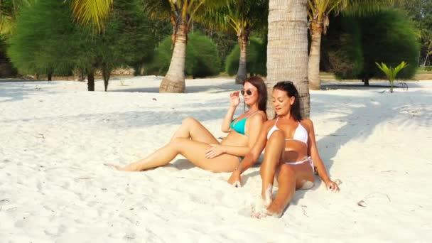 Két fiatal barátnő bikiniben ül a homokos tengerparton a pálmafa alatt, napoznak és beszélgetnek. Gyönyörű nők pihennek trópusi üdülőhelyen