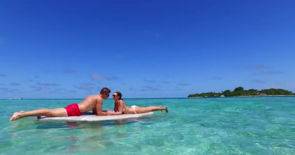 Amazing couple on paddleboard surfboard surfing together in ocean sea in Maldives