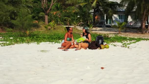 Két fiatal barátnő ül a homokos tengerparton, zacskókkal a mellettük, nézik a térképet a jövőbeli utazáshoz és beszélgetéshez. Gyönyörű nők pihennek trópusi üdülőhelyen