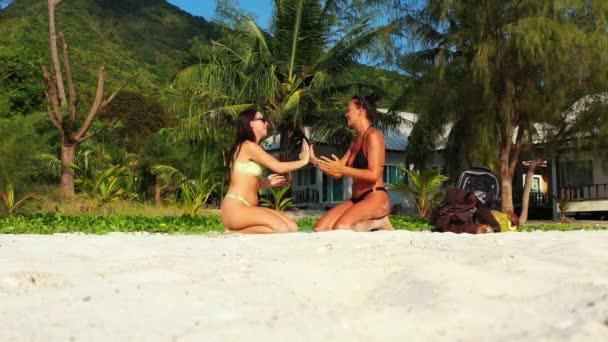 Két fiatal barátnő ül a homokos tengerparton és tapsolnak. Gyönyörű nők pihennek trópusi üdülőhelyen