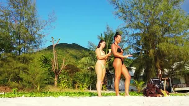 Két fiatal lány barát áll a homokos tengerparton, sundbathing és beszélgetés. Egy lány naptejszínt kent a barátnőjére. Gyönyörű nők pihennek trópusi üdülőhelyen