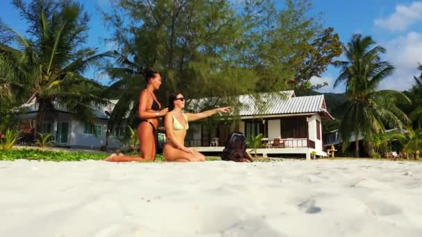 Két fiatal barátnő ül a homokos tengerparton és a vasárnapi fürdőzés. Egy lány fodrászkodik a barátnőjével. A második lány ujjal mutogat valamire. Gyönyörű nők pihennek trópusi üdülőhelyen