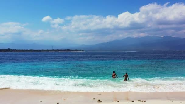 Nyári egzotikus nyaralás, a nők pihennek a fehér homokos strandon Balin