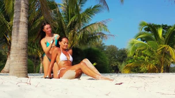 Két fiatal barátnő bikiniben ül a homokos tengerparton a pálmafa alatt és napozik. Egy lány fésülködik a barátnőjével. Gyönyörű nők pihennek trópusi üdülőhelyen