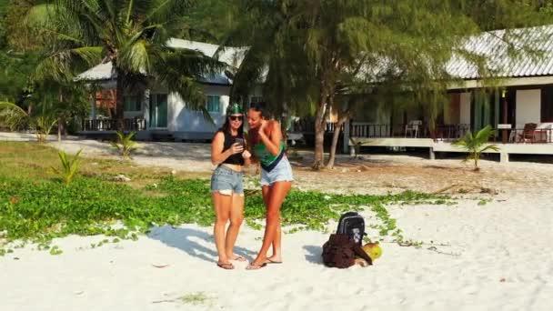 Két fiatal barátnő áll a homokos tengerparton, zacskókkal a mellettük, és néznek valamit a mobiljukon. Gyönyörű nők pihennek trópusi üdülőhelyen