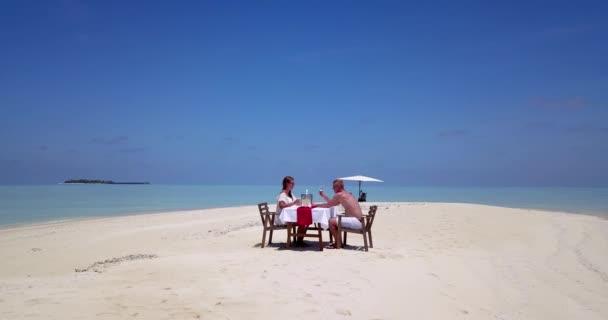 Egy pár privát ebédet tart a trópusi strandon.