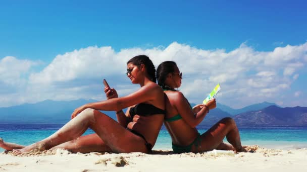 two girls having a nice time and talking and reading a brochure on the sandy beach