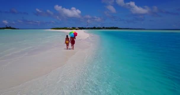 Junge Männer und Frauen spazieren mit Sonnenschirm im Meerwasser. Schönes Paar ruht sich auf tropischem Urlaubsort aus