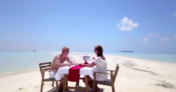 A nászutas pár egy privát, romantikus ebédet tart a trópusi strandon.