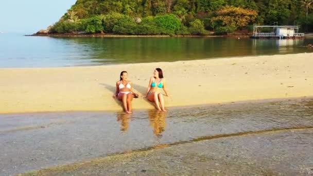 Két fiatal barátnő bikiniben fekszik a tengerparton, napoznak és beszélgetnek. Gyönyörű nők pihennek trópusi üdülőhelyen