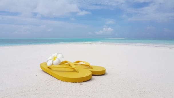 Yellow flip-flops with frangipani flower on the beach. Nature scenery of Antigua.