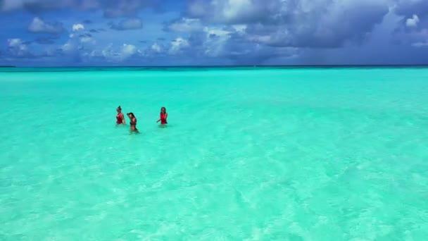 Luftaufnahme der schönen jungen Mädchen, die am tropischen Strand schwimmen