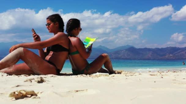 dvě dívky mají příjemný čas a povídání a čtení brožury na písečné pláži