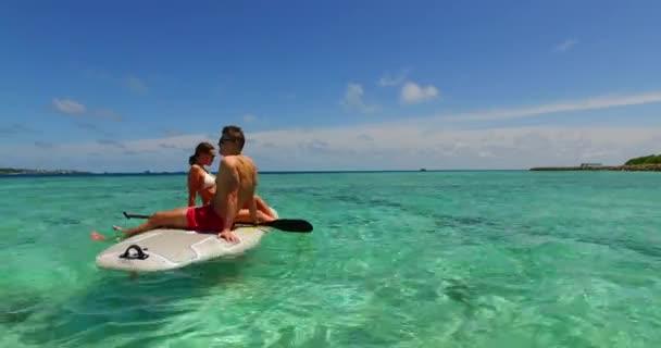 Gyönyörű pár szörfdeszkán szörfözik a Bali-tengeren.