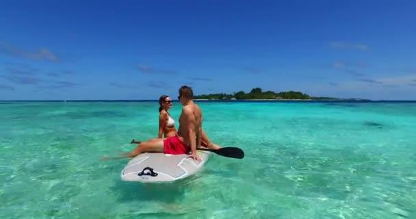 Krásný pár na surfu surfování v čistém oceánu moře na Bali