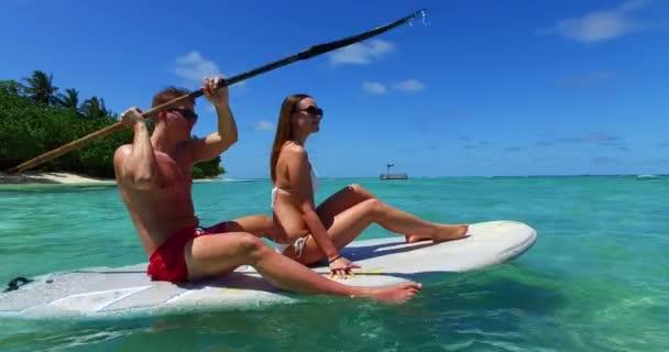 Lovely couple on surfboard surfing in clear ocean sea on Bali