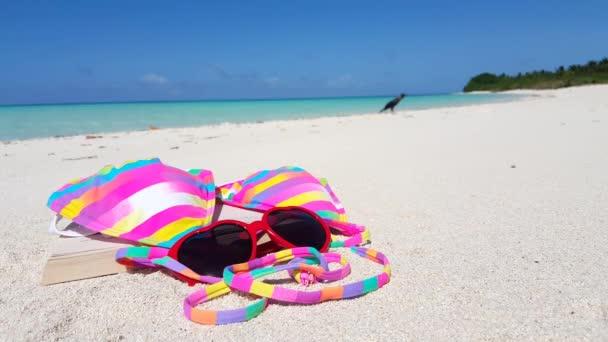 Sunglasses with striped bikini bra and opened book on the beach. Enjoying summer vacation on Bali, Indonesia.