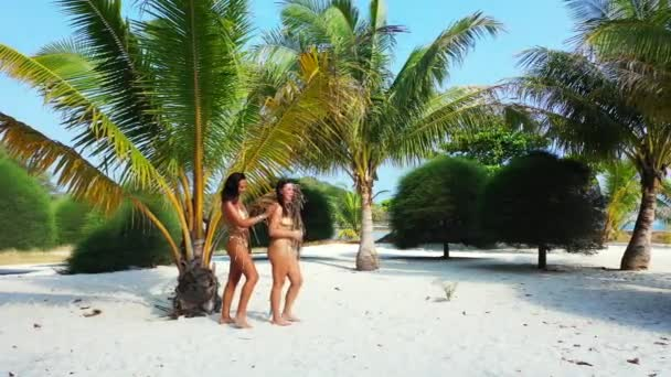 Két fiatal barátnő bikiniben áll a homokos tengerparton a pálmafa alatt és napozik. Egy lány naptejszínt kent a barátnőjére. Gyönyörű nők pihennek trópusi üdülőhelyen