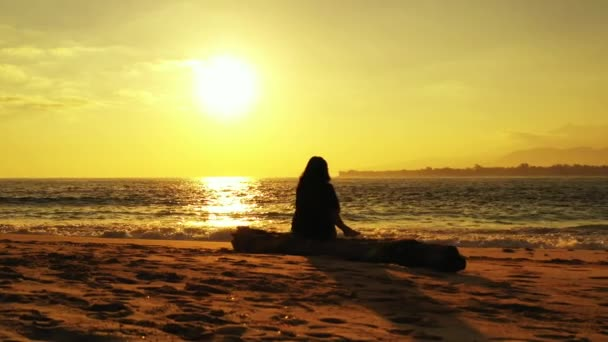 silhouette of woman relaxing on the beach at sunset