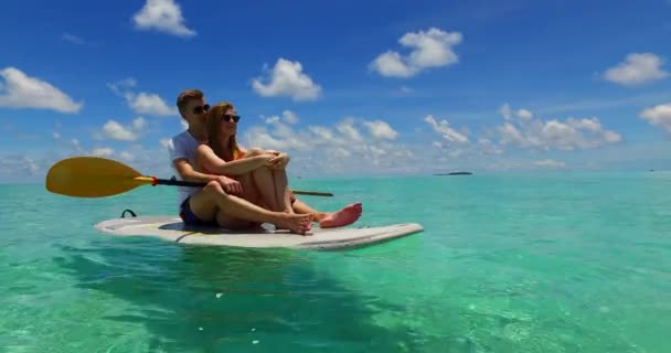 Young couple on surfboard surfing together in turquoise ocean sea in Dominican Republic