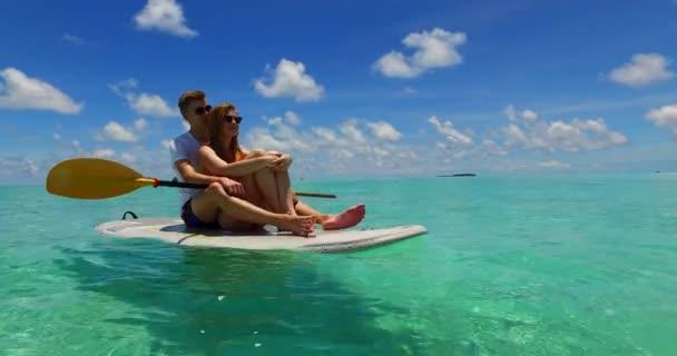 Fiatal pár szörfdeszkán együtt szörföznek a Dominikai Köztársaságban a türkiz óceáni tengeren