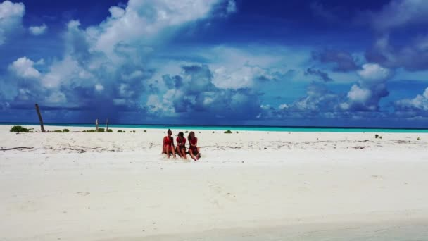Beautiful young women in bikini relaxing in the beach with clear sea and blue sky. Travel in holiday vacation in Maldives.
