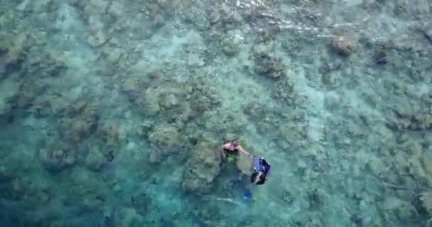 Young happy couple swimming and snorkeling on crystal clear water in Maldives. Enjoying summer exotic vacation.