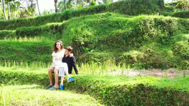 Video of attractive girl sitting on boyfriend knees in green field of tropical island