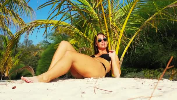 Girl in black swimsuit resting and sunbathing on beach, summertime leisure concept footage