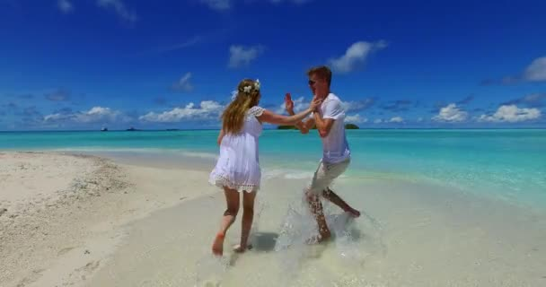 Beautiful virgin shore of the blue sea and white sand beach. Couple relaxing on vacation in Maldives.