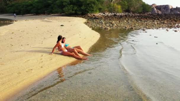 Két fiatal barátnő bikiniben fekszik a tengerparton és napozik. Gyönyörű nők pihennek trópusi üdülőhelyen