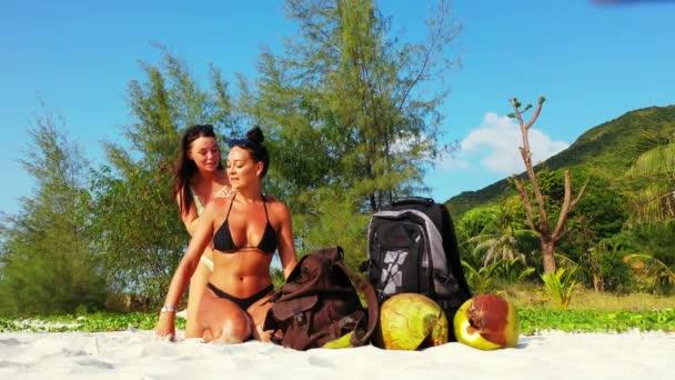 Két fiatal barátnő ül a homokos tengerparton, fürdőznek és beszélgetnek. Egy lány naptejszínt kent a barátnőjére. Gyönyörű nők pihennek trópusi üdülőhelyen