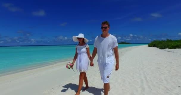 Mladý muž a žena kráčející po písečném pobřeží. Krásný pár odpočívající na tropické letovisko