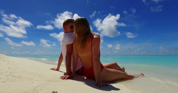 šťastný pár sedí na tropické pláži