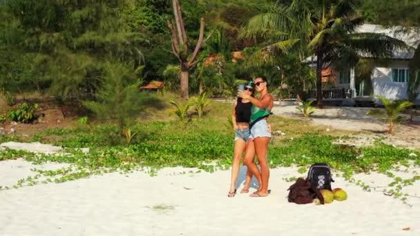 Két fiatal lány barátok áll homokos tenger partján zacskók mellettük, és csinál szelfi okostelefonon. Gyönyörű nők pihennek trópusi üdülőhelyen