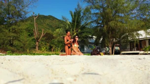 Két fiatal barátnő ül a homokos tengerparton és a vasárnapi fürdőzés. Egy lány fodrászkodik a barátnőjével. Gyönyörű nők pihennek trópusi üdülőhelyen