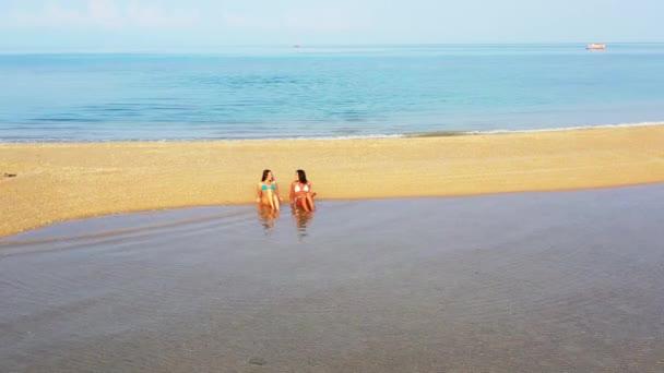 Két fiatal bikinis barátnő fekszik a tengerparton. Gyönyörű nők pihennek trópusi üdülőhelyen
